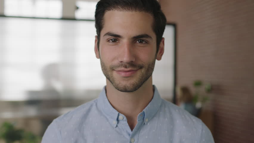 Close up portrait of young successful middle eastern businessman looking at camera smiling happy in office workspace background real people series | Shutterstock HD Video #1012023851