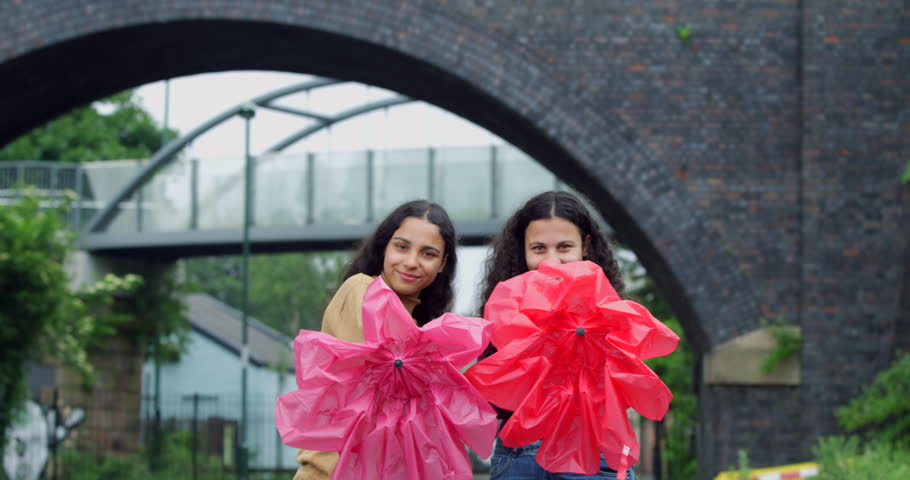 Portrait of beautiful Smiling Young Mixed Race Women with Umbrellas. Multi-Racial Curly hair Teen girls having fun and playing against Inner City bridge and town housing. Pretty student friends joking
