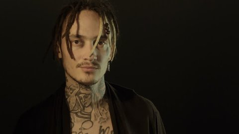 Tattooed man loking to the camera. Addiction concept. Man with Tattoos and dreds.
