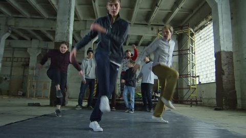 Group of three teenager friends dancing to hip hop music on the floor in an abandoned building, their friends standing in the background
