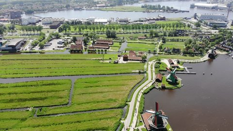 ZAANSE SCHANS, NETHERLANDS - JUNE 05, 2018: Drone aerial view of the traditional and typical dutch windmills and polder landscape of the Zaanse Schans