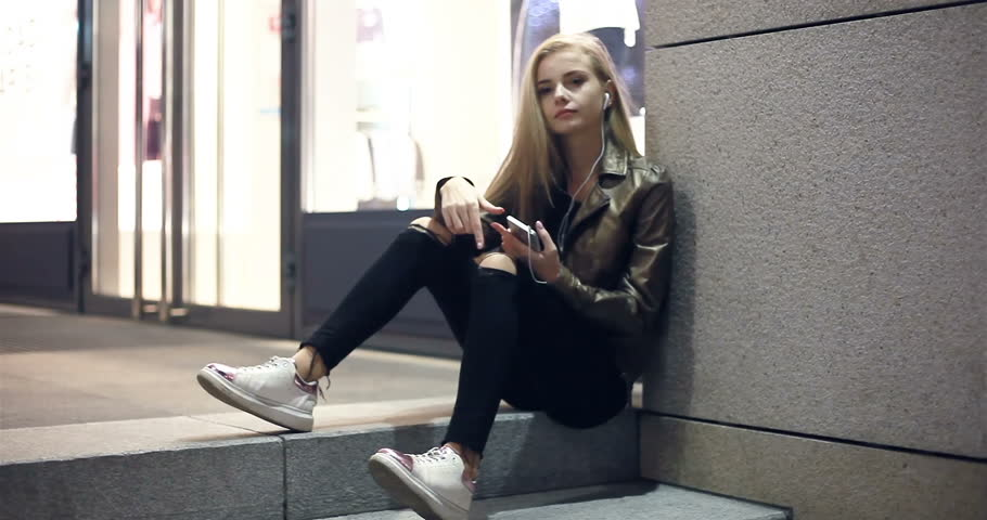 Teenage girl with long blonde hair walking along the street,listening to the music,dancing, smiling, wearing headphones at night under red lights. Tracking shot. | Shutterstock HD Video #1012041581