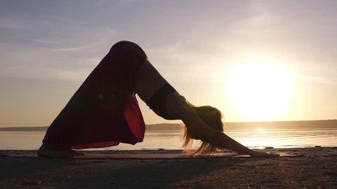 Beautiful footage on sunset beach, woman doing yoga asana on a mat, backbend, Urdhva Mukha Shvansana. Slow motion