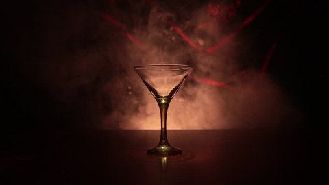 Slider shot. Glass with martini with olive inside. Close up view of glass with club drink on dark foggy toned background. Selective focus. Alcohol drink poured into martini glass of bottle