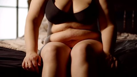 concept of obesity. girl in underwear sitting on the edge of the bed big fat folds with wrinkles and cellulite