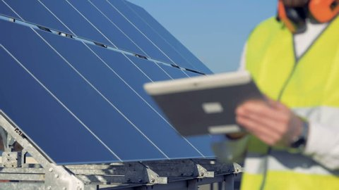 Green energy concept. Close up of a tablet computer in the hands of a solar module's constructor