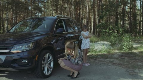 Frustrated woman calling for assistance after car broken down during summer vacation road trip. Desparate female driver with smart phone calling for help while standing near broken car on roadside.