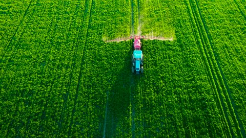 Aerial view of farming tractor plowing and spraying on green field
