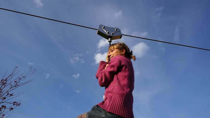 Little beautiful girl is riding zipline. Zipline or trolley is rope stretched at certain angle along which, with carbine or block, people move under gravity.