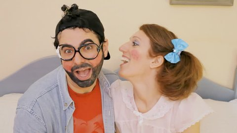 An odd couple (actors in character as kids): a girl licking the ear of a guy as foreplay for sex. Funny close-up shot.