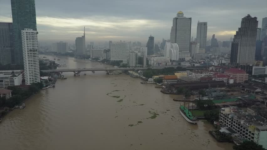 Bangkok River drone view in 4K. Chao Phraya is the major river in Thailand and this clips gives a bird's eye perspective of the water stream, boat traffic and surrounding buildings and skyscrapers  | Shutterstock HD Video #1012159151