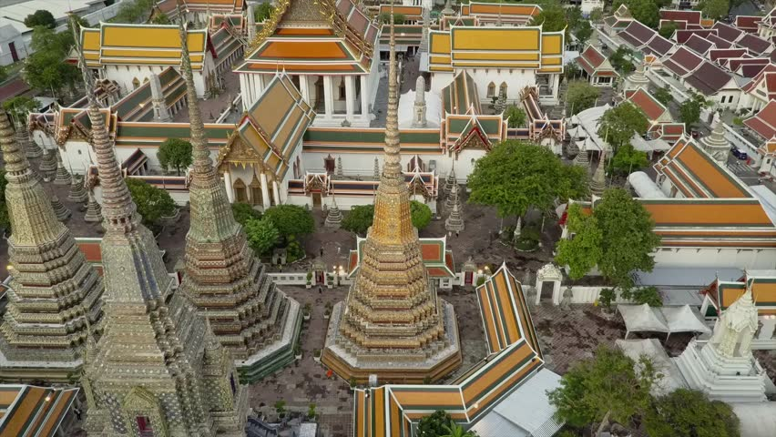 Wat Phra Kaew temple drone views in 4K. Golden light before sunset aerial views of Thai Buddhist temple in Bangkok