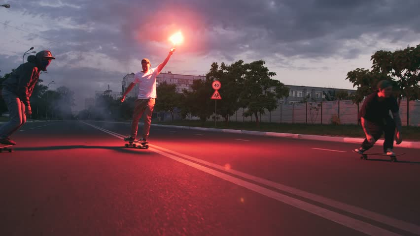 Group of young people skateboarding on the road in the early morningwith red sugnal flare, slow motion