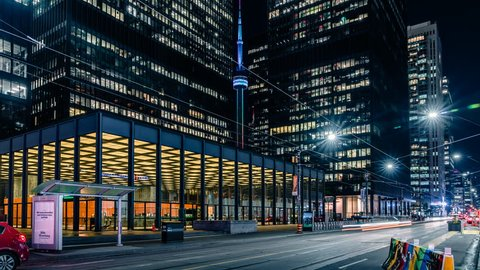 Toronto, Ontario / Canada - June 2 2018: Time lapse of the modern and futuristic Toronto financial district with smooth beautiful car traffic light streaks and epic architecture. Cn Tower and TD bank.