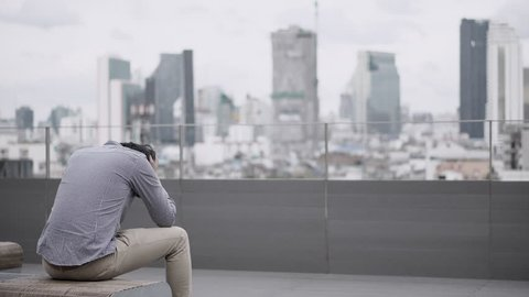 Young Asian business man feeling stressed and frustrated with job and life problems sitting on bench on office building rooftop terrace. city view in background. Major depressive disorder concept.