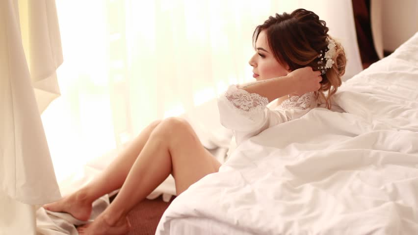 Happy bride in a white peignoir sits and straightens her hairstyle in the bedroom in her wedding day.