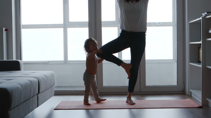 Mom is standing on one foot on a rug for yoga next to her daughter | Shutterstock HD Video #1012196531