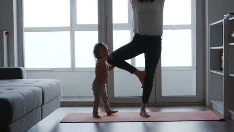 Mom is standing on one foot on a rug for yoga next to her daughter