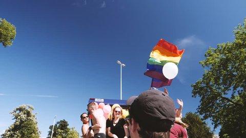 STRASBOURG, FRANCE - JUN 10, 2017: Majestic gay flag waving as gay friends are dancing on truck during gay pride in France, Strasbourg - annual LGBT pride FestiGays