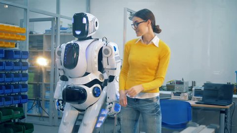 Young woman is slapping a human-like robot after it spanks her playfully