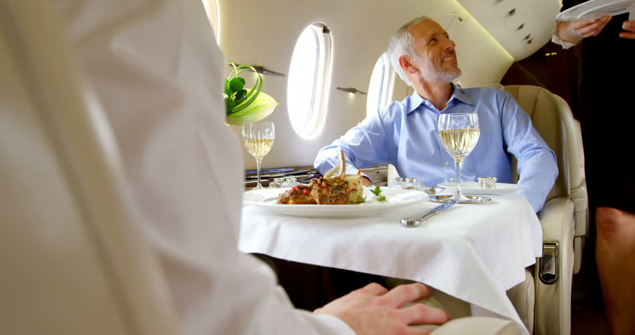 Flight attendant serving meal to businessmen in private jet 4k
