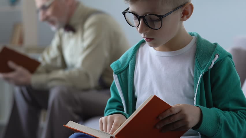 Funny small kid in glasses reading book with happy grandfather behind, bookworm