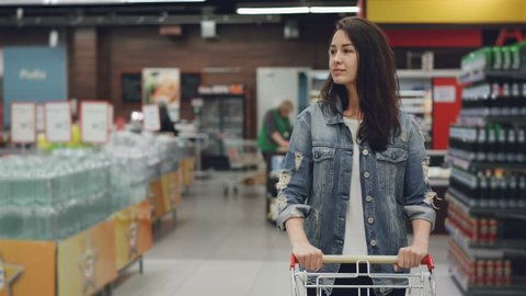 Pretty young lady is walking through aisle in supermarket with shopping cart looking at shelves with products, employees in uniform are working in background.