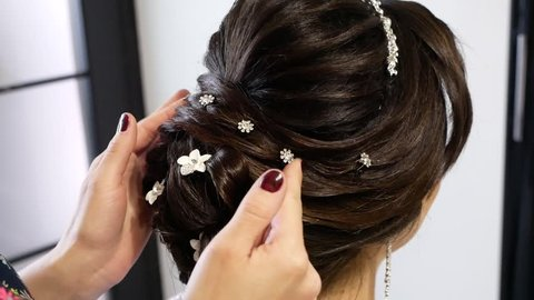 Beauty wedding hairstyle. Bride. Brunette girl with curly hair styling with barrette.
