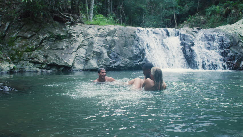 Handsome guy jumping into water with friends near waterfall in rainforest. Shot with a RED camera. 4k footage.