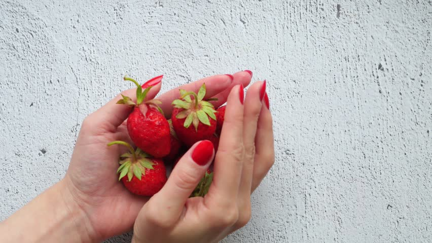 A girl holds a strawberry in her hands and shows it. Close-up. Red juicy berry in hands.
