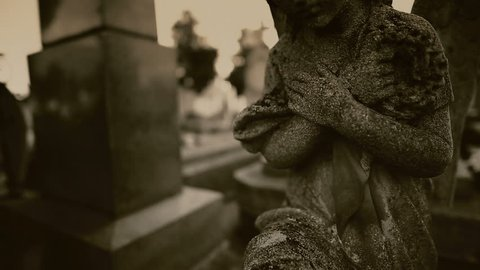 Statue of an angel praying in a cemetery.Funeral concept.