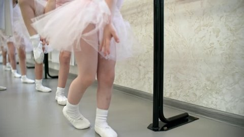 Legs of unrecognizable little girls using ballet barre to stretch legs for splits, their teacher helping them, dolly shot, camera moving forwards
