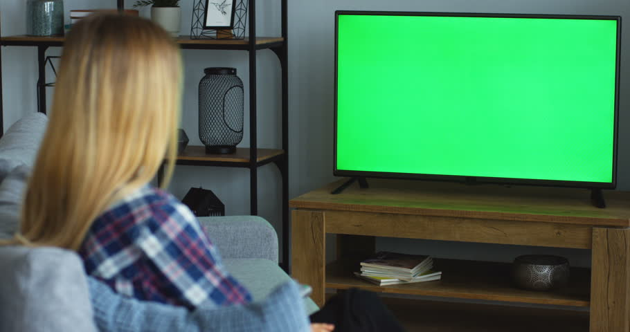Rear of the blonde woman in the motley blue shirt sitting on the gray couch in the living room, watching TV with green screen and changing channels with a remote control. Chroma key. Inside | Shutterstock HD Video #1012385321