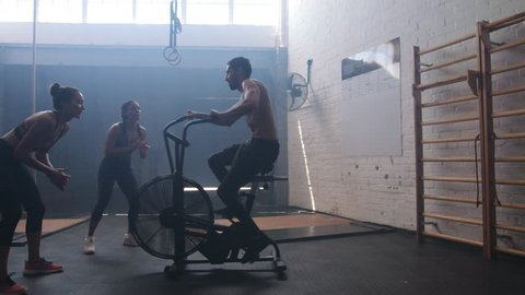 Muscular young man exercising on air bike in gym with female friends motivating him. Male using air bike for workout at cross training gym with friends.