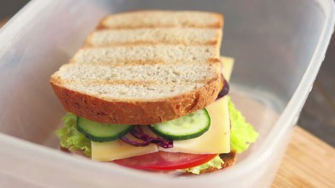 man open plastic food container lunch box with tasty sandwich