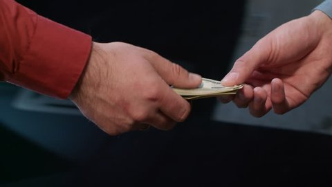 Money transfer from hand to hand. Close up of business man hands transfer money. Successful business deal concept. Business handshaking. Cash money transfer concept. Quick and easy cash service