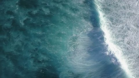 Big Waves rolling from above in Oahu, Hawaii Top down 4k drone view on blue turquoise ocean, breaking waves and whitewash. Sunny day over the sea. Huge swell and foaming on North Shore
