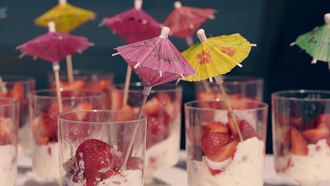CU, Slow motion, Travelling around: Fresh cocktails are on the table, on the beach, in the summer. Decorated with colorful umbrellas. With berries and fruits.