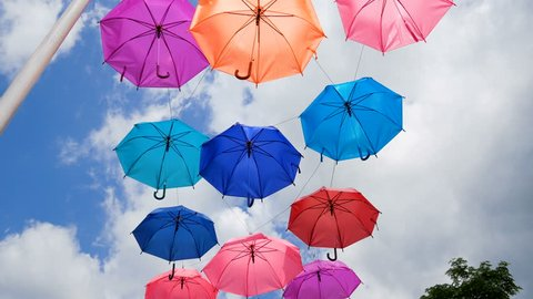 Colorful umbrella hanging against cloudy blue sky