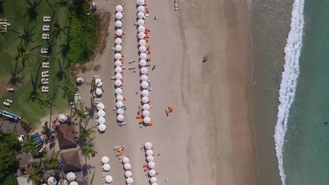 Beach top down. Tourist under parasol, beach, swimmers, sunbathing, palm trees and lifeguard. Colourful sunshades. beautiful bay. aerial drone shot from above