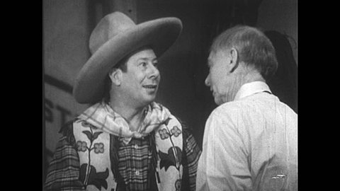 1930s: Justice of the peace pats cowboy on the back. Cowboy and justice of the peace speak. Cowboy smiles. Justice of the peace pins badge on cowboy's vest.