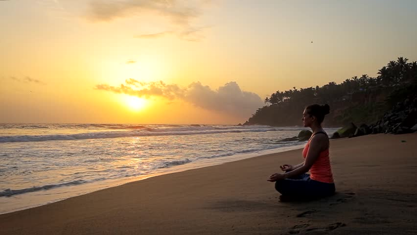 Woman doing yoga - meditate and relax in Padmasana Lotus asana pose with chin mudra outdoors at tropical beach on sunset | Shutterstock HD Video #1012478891