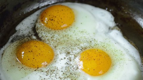 Cooking Fried eggs. Process of Preparation of Three Fried Egg. Time Lapse. Top view. Full Cycle of Frying Eggs: Break Eggs into a Hot Frying Pan, Salt, Pepper, Remove Eggs from a Frying Pan