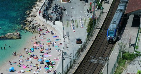 Villefranche-sur-Mer, France - May 20, 2018: Beautiful Aerial View Of The Bay Of Villefranche-sur-Mer, People Sunbathing On The Beach, Mediterranean Sea With Clear Water And Train (ter SNCF). 4K Video