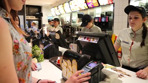 KYIV, UKRAINE, JUNE 14, 2018: The courteous cashier serves the client in McDonald's