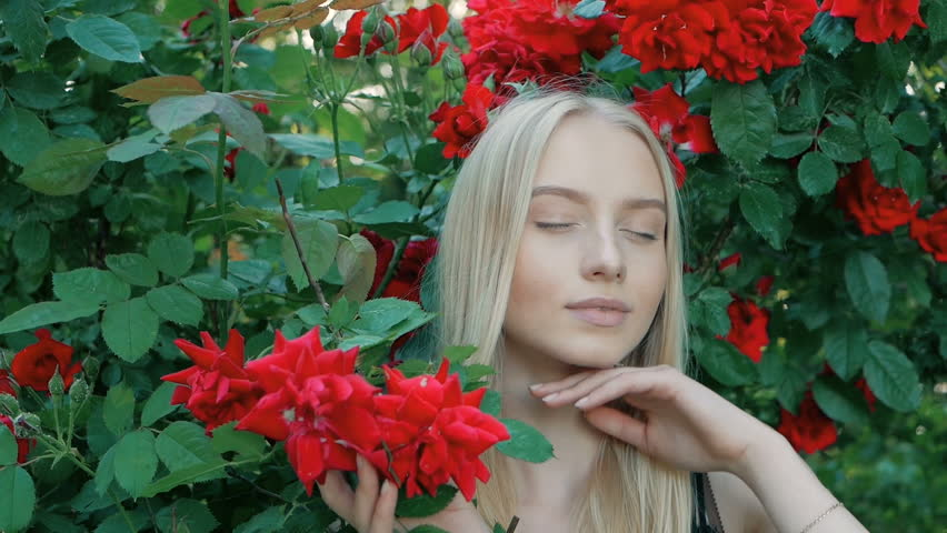 Beautiful fashionable portrait of a young woman with blue eyes and blonde hair in a outdoors in red rose garden | Shutterstock HD Video #1012515851