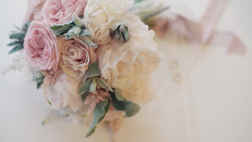 Wedding rings lie near beautiful wedding bouquet on the white floor
