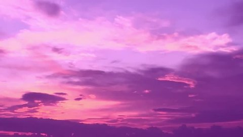 Clouds with orange, purple and black colors at sunset sky. Telephoto video of dramatic pink and purple clouds at sunset. 4K.
