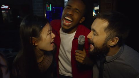 Close up faces of ecstatic young people of different ethnicities looking at camera when singing into microphone during party in nightclub