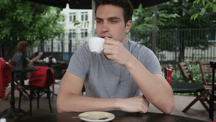 Young Man Drinking Coffee while Sitting in Cafe Terrace | Shutterstock HD Video #1012557911